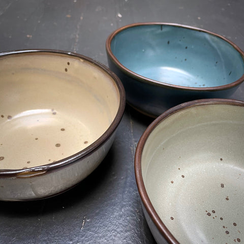 Set of three bowls in blue, cream, green