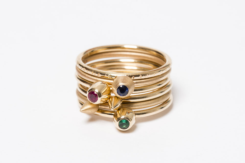 A stack of six gold rings, three with gemstone settings in the shape of buds, two with small spike shapes attached and one with a hammered texture.