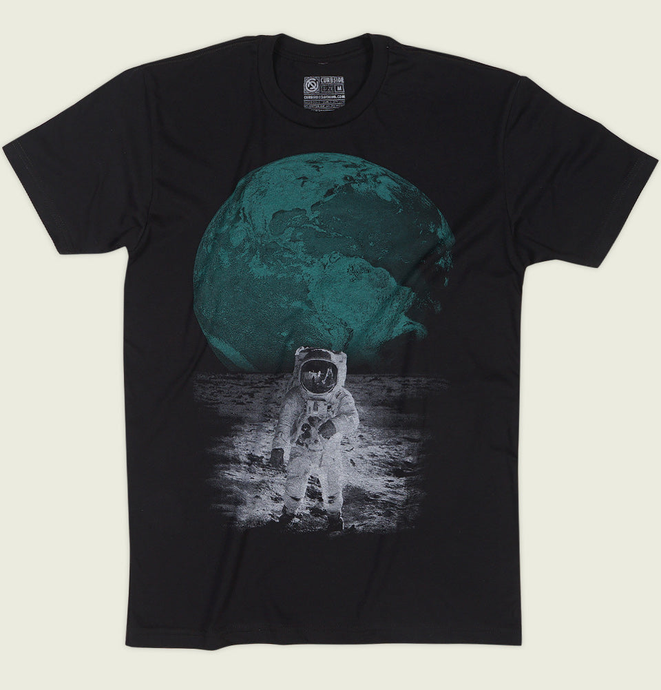 Men T-shirt by Curbside Clothing with Astronaut Walking on the Moon Showing Earth Behind on Black Unisex Graphic Tee Shirt Showing Wrinkled Tshirt Front - Tees.ca