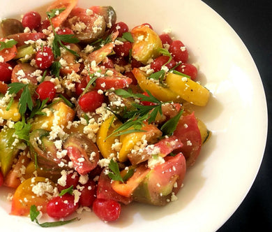 Fresh yellow, orange and red heirloom tomatoes with fresh herbs and crumbled feta with a champagne vinaigrette (GF)