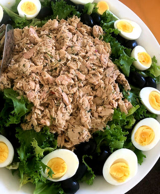Herb-marinated tuna on a bed of curly endive with sliced hard-boiled eggs with oil-cured olives with a Romesco vinaigrette (GF)