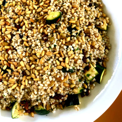 Israeli cous cous and barley salad with tomato, grilled zucchini, golden raisins, pine nuts, capers and fresh herbs