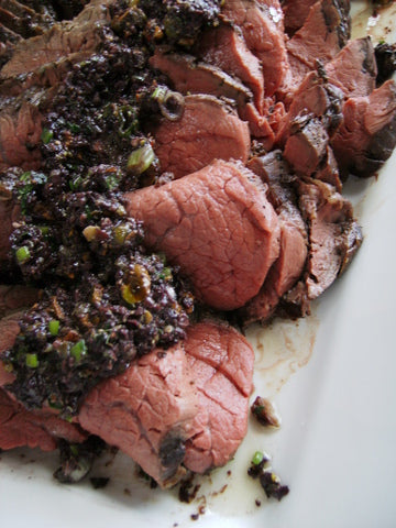 Roasted filet mignon with a sauce of black olives, capers, garlic, pistachios, fresh herbs, lemon and extra-virgin olive oil