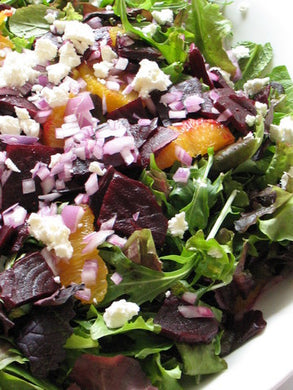 Salad of baby greens with roasted beet, citrus, red onion and goat cheese in a raspberry vinaigrette