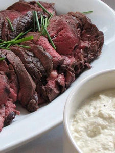 Platter of sliced filet mignon, fresh herbs and a horseradish cream on the side