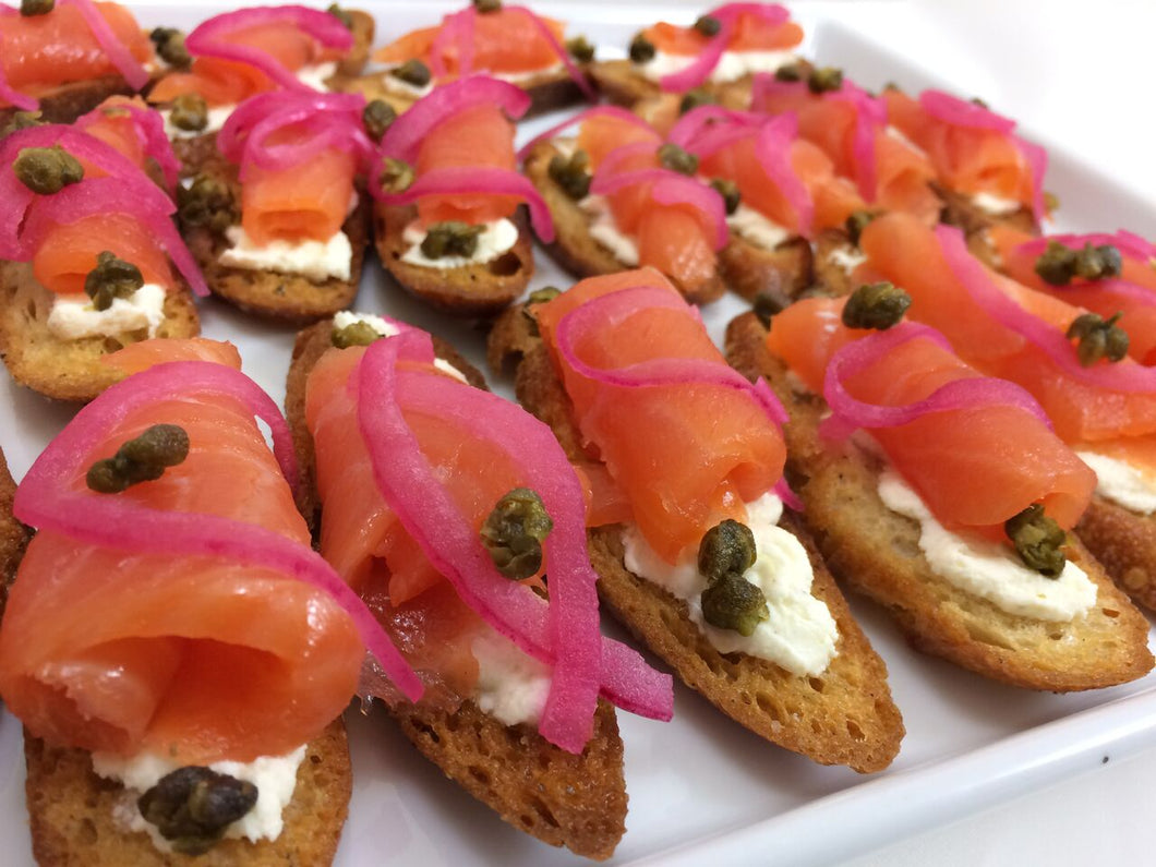 Miniature smoked salmon tartine with fromage blanc, lemon, shaved red onion and capers