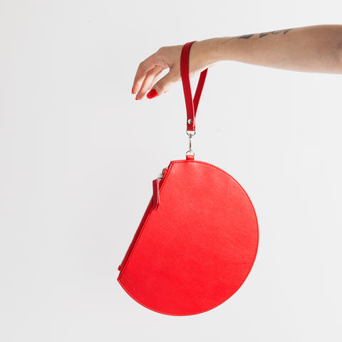 3/4 Moon Clutch in Red Model Holding Wrist Strap
