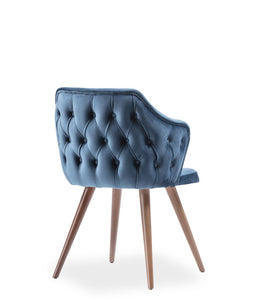 Fully upholstered blue armchair. Rounded back with tufting on the outside, angled wood legs. Back 3/4 view.