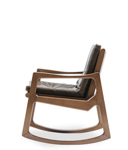 Mid-century styled rocking chair. Dark wood frame and thick leather cushions. Side view.