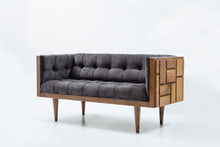 Modern sofa with tufted leather upholstery. Exterior wood shell with carved geometric patterns of repeating squares. 3/4 Front view.