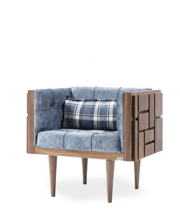 Modern armchair with tufted leather upholstery. Exterior wood shell with carved geometric patterns of repeating squares. 3/4 Front view.