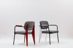 Graphic armchair with 2-toned frame and geometric back legs. Padded seat and back. Double front 3/4 view.