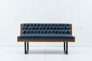 Modern sofa with tufted leather upholstery and u-shaped metal legs. Exterior wood shell and edgeing. Front view.