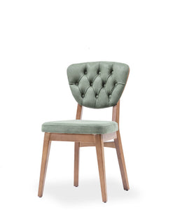 Dining chair with sage green tufted back and upholstered seat. Wood frame and legs. Front 3/4 view.