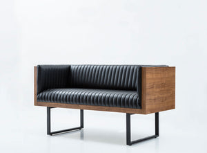 Modern sofa with vertical seamed leather upholstery. Exterior wood shell and edges, metal u-frame legs. Front 3/4 view.