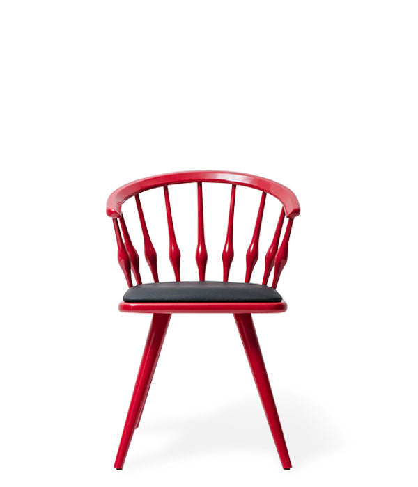 Red painted wood chair with round spindle back, angled legs and black seat pad. Front view.