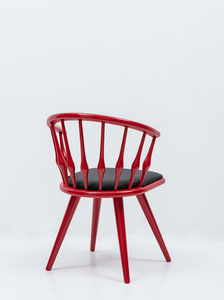 Red painted wood chair with round spindle back, angled legs and black seat pad. Back 3/4 view.