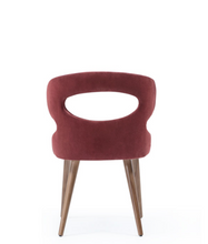 Modern wrap around chair, fully upholstered with an oval cut out. Back view.