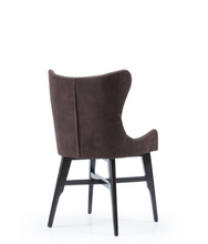 Short-backed wingback chair. Brown fabric and wood legs with x-shape cross bars. Back 3/4 view.