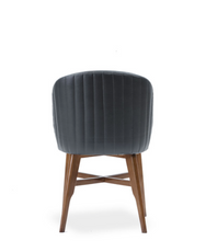 Rounded back tub chair. Leather upholstery with vertical seam detail on back of seat. Wood legs with cross bar details. Back view.