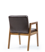 Clasic square armchair woth leather cushioned seat and back and a wood frame. Back 3/4 view.