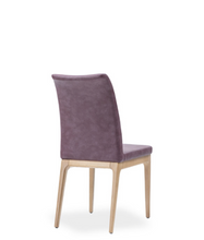 Mauve fabric covered dining chair with wood legs. Chair back curves back slightly. Back 3/4 view.