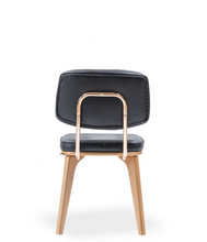 Modern chair, light wood legs and black leather seat and back. Back view.