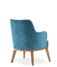 Large blue upholstered chair, curved back with arms and wood legs. Back 3/4 view.