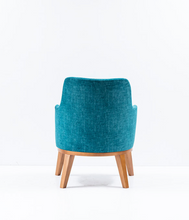 Large blue upholstered chair, curved back with arms and wood legs. Back view.