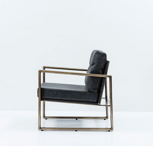 Modern angular arm chair with steel frame and black leather cushions. Side view.