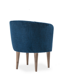 Large blue upholstered chair, round seat and curved back with rolled edge. Back 3/4 view.