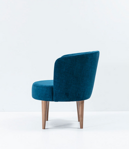 Large blue upholstered chair, round seat and curved back with rolled edge. Side view.