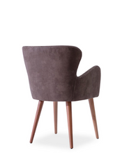 Short backed wingback chair with arms. Brown fabric and wood legs. Back 3/4 view.