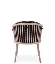 Pale wood frame tub chair with spindle construction and removable black cushions. Back view.