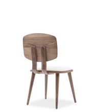 Wood dining chair with lozenge shaped, veneer wrapped back and white seat and back pads. Back 3/4 view.