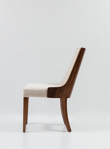 Cream fabric covered dining chair with curved wood legs and wood veneer back. Chair back curves around the body slightly. Side view.