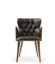 Dark leather tufted chair, wingback style. Front view.