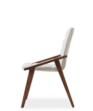 Architectural white leather upholstered armchair. With slanted arms and solid dark wood frame. Side view.