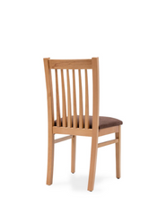 Natural wood dining chair with brown fabric seat and spindles on the back. 3/4 back view.