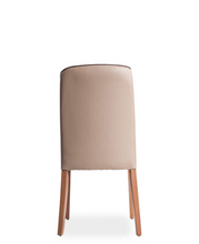 Taupe  fabric covered dining chair with wood legs and piping. Chair back curves around the body slightly. Back view.
