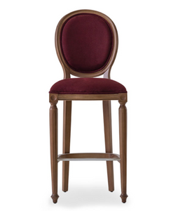 Traditional style bar stool with an oval back and carved wood frame and legs. Brown upholstery, front view.