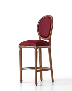 Traditional style bar stool with an oval back and carved wood frame and legs. Brown upholstery, 3/4 front view.