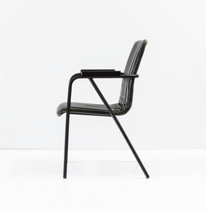 Black modern style chair with metal frame and arms. vertical seam details with back and seat. Side view.