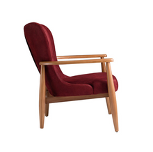 Low, red armchair. Wood frame and legs with a streamlined wingback shape. Side view.