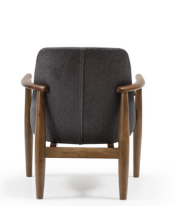 Low armchair with thick grey upholstery and a turned dark wood frame. Back view.