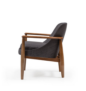 Low armchair with thick grey upholstery and a turned dark wood frame. Side view.