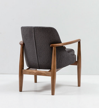 Low armchair with thick grey upholstery and a turned dark wood frame. Back 3/4 view.