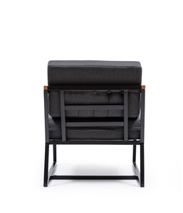 Architectural armchair with black metal frame. Thick grey cushions and wood arms. Back view.