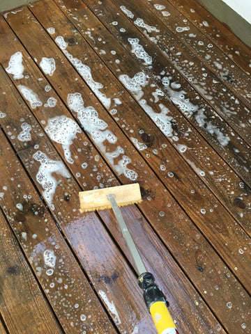 Scrub the wood deck with a brush to work the W99 detergent cleaner