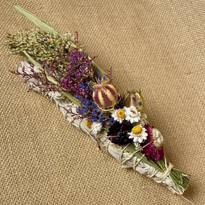 These Organic Dried Flower and Desert Sage Smudge Sticks are made from sustainably harvested California Desert Sage to which assorted organic dried wildflowers have been added. Burning sage, known for its healing and energetic cleansing properties, helps to release negative vibrations, lift consciousness, and bring about new life.